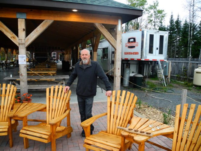 Raquette River Brewery co-owner Mark Jessie stands in front of the bar and restaurant's iconic pavilion which will be enclosed by the winter months. A utility building built where the food truck now stands will heat the pavilion's floors while the truck will be moved to the opposite side of the property. (Enterprise photo — Aaron Cerbone)