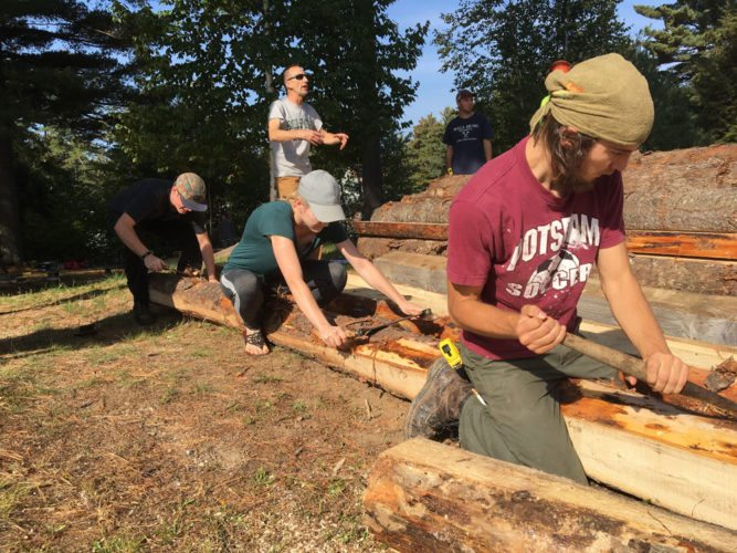 North Country Community College student Paige Hart, center, and Paul Smith's College students Mike Gaulin, rear, and Tim Otis, peel bark off a log that will become part of a new lean-to at the NCCC Saranac Lake campus. (Photo provided)