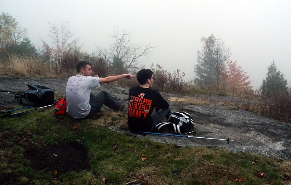 Jordan Hosmer and Stephen Cerbone stare into the fog as they sit on the top of Haystack Mountain after knocking the Saranac 6er peak off the list of mountains needed to complete the 6er Relay. (Enterprise photo — Aaron Cerbone)