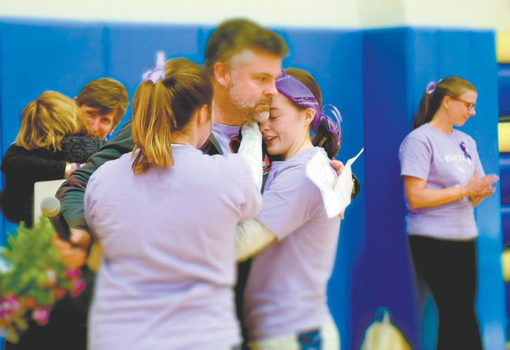 Sara McKillip, right, and her sister Kaleigh McKillip, hug their father Dave before Monday night's home volleyball match against Peru. Sara McKillip, a 15-year-old sophomore and member of the Blue Bombers volleyball team was recently diagnosed with Hodgkin's Lymphoma, and was honored with a sea of purple shirts and ribbons worn by players and spectators. Pictured at back is LakePlacid coach Donna Moody hugging Sara McKillip's mother. (Enterprise photo — Justin A. Levine)