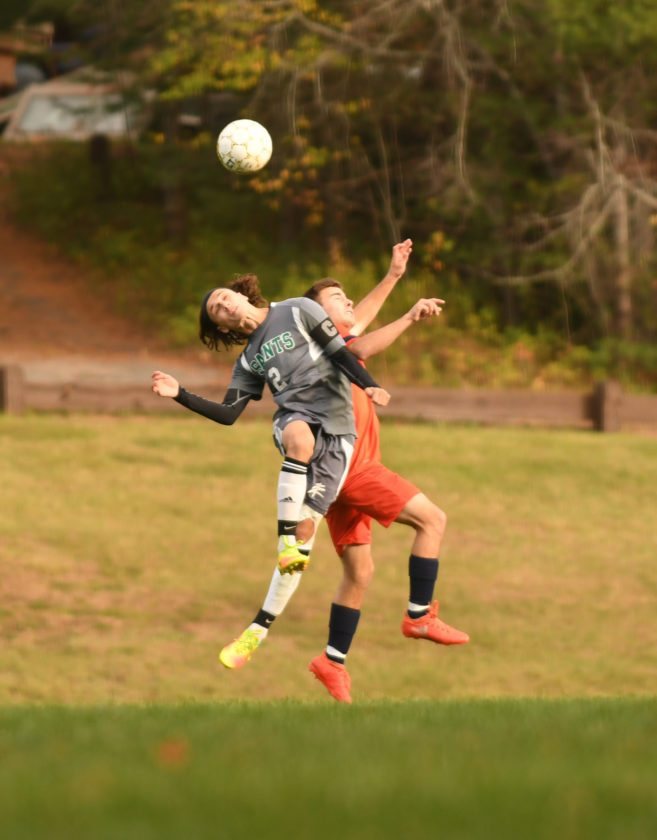 North Country's Sim Marhatta battles with a Clinton opponent for a head ball in Tuesday's match. (Enterprise photo — Lou Reuter)