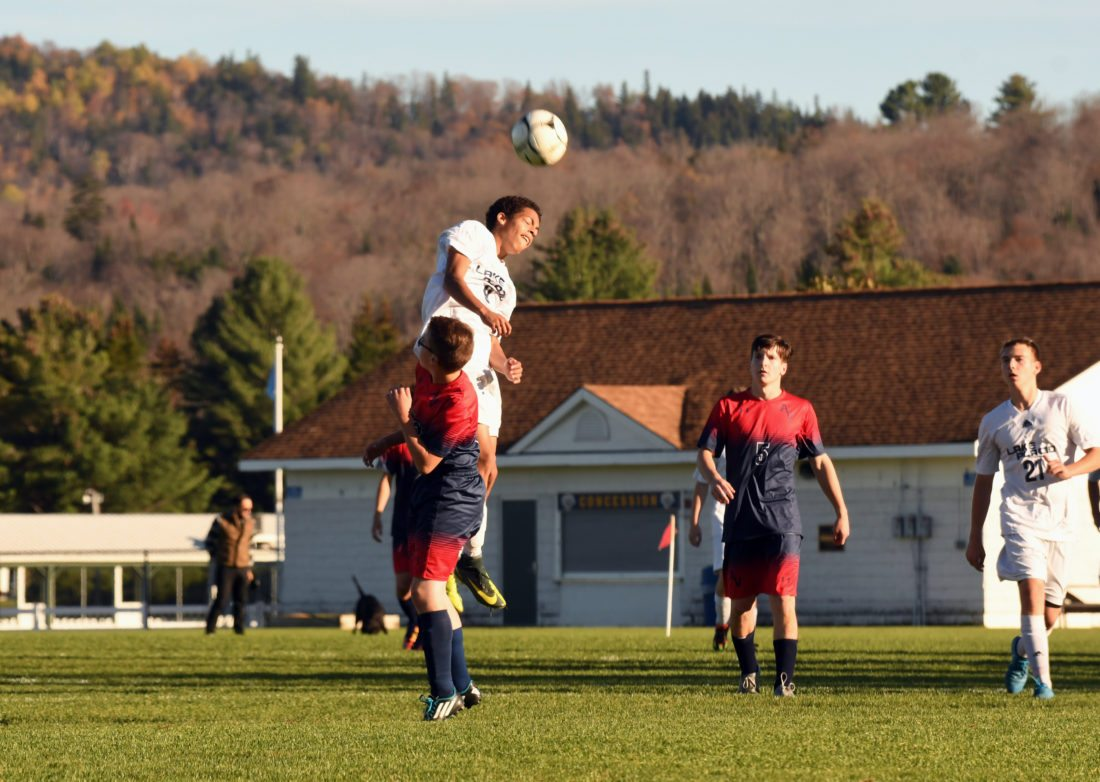 Lake Placid's Jarell Paul heads  the ball over AuSable Valley's David Janisse during the second half of Wednesday's match. Also pictured are Cobane Bissonette of Lake Placid and Patriots' forward Caleb Hamilton. (Enterprise photo — Lou Reuter)