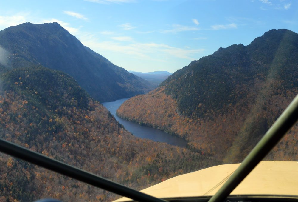 Lower AuSable Lake is in view through the windshield of Bob Rose's 1949 Piper Clipper airplane, the Colvin Range at left and Sawteeth Mountain at right. (Enterprise photo — Antonio Olivero)