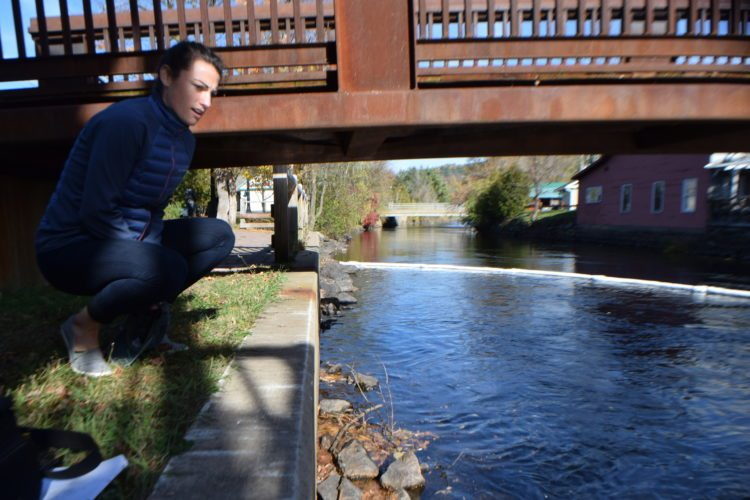 Erin Hanczyk, a public participation specialist with the state Department of Environmental Conservation, looks at an oil sheen on the Saranac River Thursday afternoon in downtown Saranac Lake. (Enterprise photo — Glynis Hart)