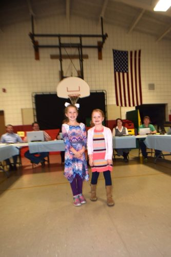 First-graders Leighton Tomasewski and Josie Martin show the Saranac Lake school board how they use the SeeSaw app to share their schoolwork with their parents. (Enterprise photo — Glynis Hart)