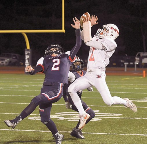 Saranac Lake receiver Emery Swanson leaps above a Patriots defender to haul in a 31-yard pass from quarterback DJ Morgan in the opening quarter of Friday's game in Clintonville. (Enterprise photo — Lou Reuter)