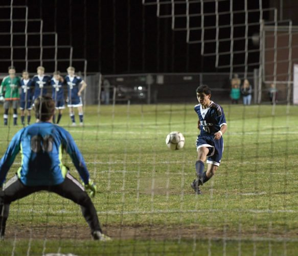 With his Lake Placid teammates watching in the background, Joaquim Benavides buries his attempt past Seton Catholic goalkeeper Tyler Reid during the shootout round in Monday's match.  (Enterprise photo — Lou Reuter)
