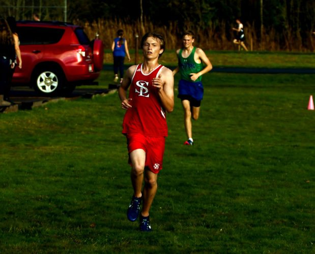 Left, Saranac Lake senior co-captain Tyler Martin closes in on the finish line ahead of Seton Catholic's Luke Moore in Tuesday's high school cross country meet on the Red Storm's course. (Enterprise photo — Lou Reuter)