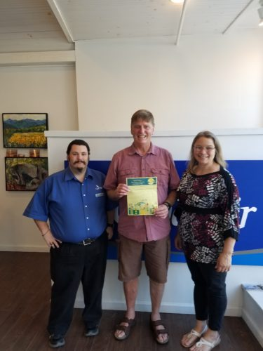 Bill Rich of Saranac Lake is presented with his voucher for two round trip Cape Air tickets from Saranac Lake to Boston by Aleacia Landon, director of the Saranac Lake Youth Center.  Bill won the tickets in a drawing during the Olga Memorial Footrace in August. Also pictured is Cape Air ticket agent Jesse.  (Photo provided)