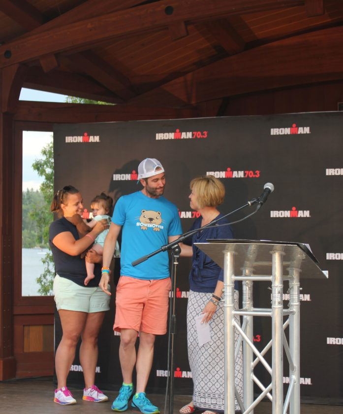 Ryan Heisler presents a check to Sylvia Getman, Adirondack Health president and CEO, at the 2017 Ironman Lake Placid opening ceremony, while Heisler's wife, Kelly Burns Gallagher, and their daughter, Ivy, look on. (Photo provided)