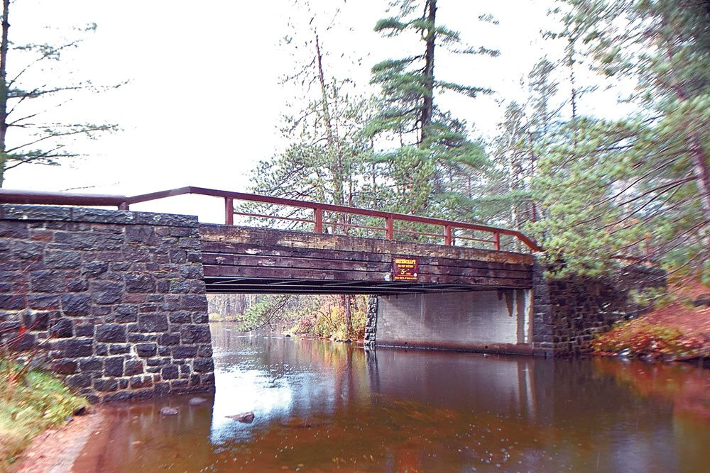 """Campsite Road at Fish Creek State Campground passes over its namesake stream on this bridge, built in 1935 but still rated at a 67.7 sufficiency. Despite being sound, its stone and log construction and steel deck render it """"functionally obsolete."""" (Enterprise photo — Glynis Hart)"""