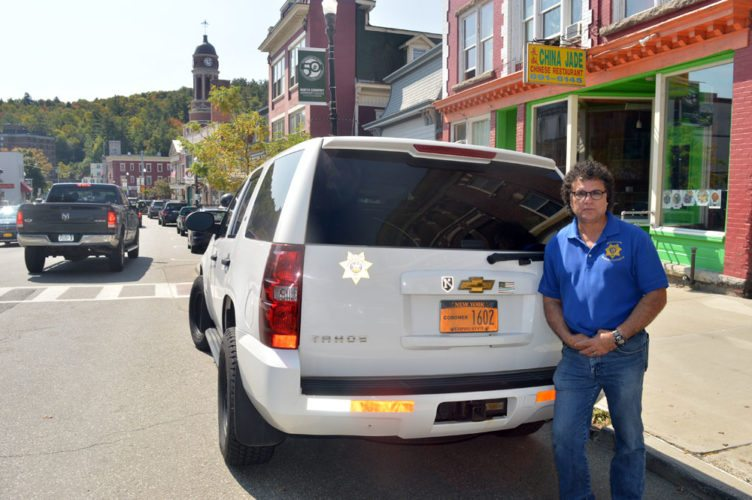 """Essex County Coroner Frank Whitelaw, of Bloomingdale, poses beside his Chevy Tahoe with """"coroner"""" license plates in downtown Saranac Lake. This vehicle is his own, which he paid for, along with all his coroner equipment and training courses; the county didn't pay for it. (Enterprise photo — Antonio Olivero)"""