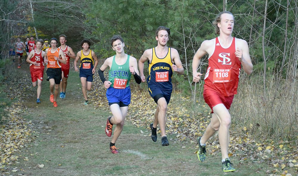 Saranac Lake senior Lauchlan Cheney-Seymour, right, leads Lake Placid's Scott Schulz and Seton Catholic's Jake Glicksman during the early part of Friday's CVAC championships in Cadyville. (Enterprise photo — Justin A. Levine)