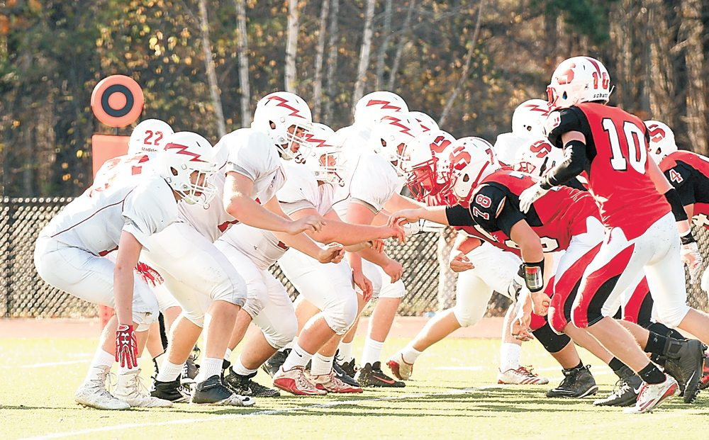 Saranac Lake's offensive line, left, takes on Saranac Central's defensive charge during a play in the second half of Saturday's Section VII, Class C championship game at AuSable Valley. The Chiefs triumphed 21-12 to capture the first title in 50 years of competing in football. (Enterprise photo — Lou Reuter)