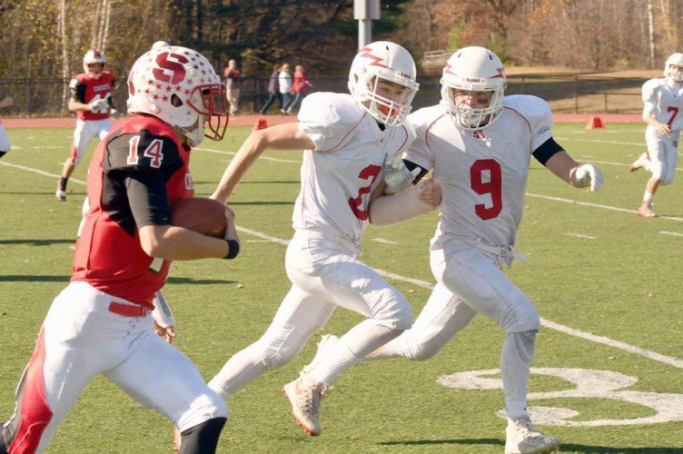 Saranac Lake defenders Jarrett Ashton, right, and Emery Swanson track down Saranac Central quarterback Luke Maye during the first half of Saturday's game in Clintonville. (Enterprise photo — Lou Reuter)