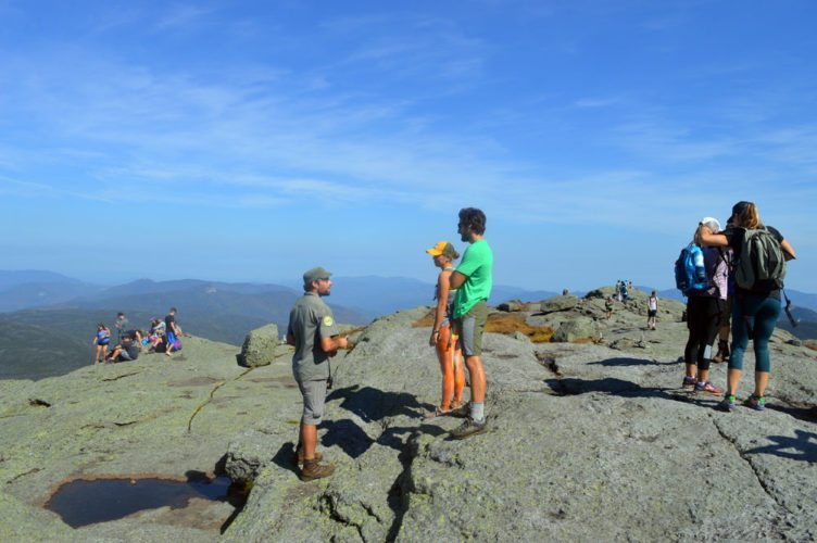 A summit steward talks to two of numerous hikers atop Mount Marcy, New York's highest point, on Sept. 23. (Enterprise photo — Antonio Olivero)
