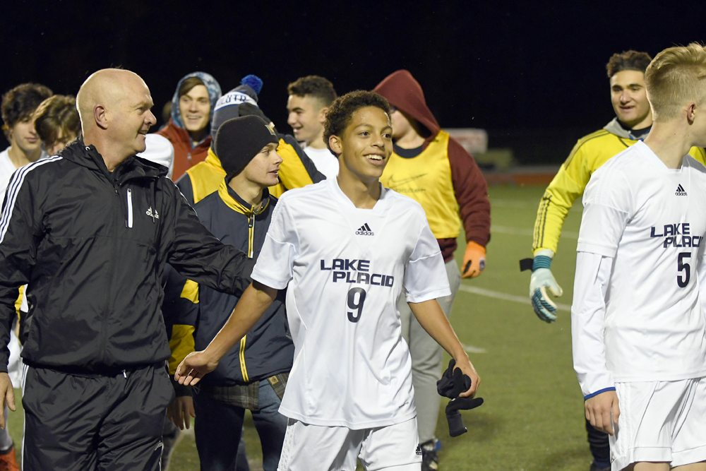 Lake Placid coach Stuart Hemsley and senior Jarell Paul (9) leave the field with the rest of the team while celebrating Wednesday's 1-0 victory over St. Lawrence Central. (Enterprise photo — Lou Reuter)