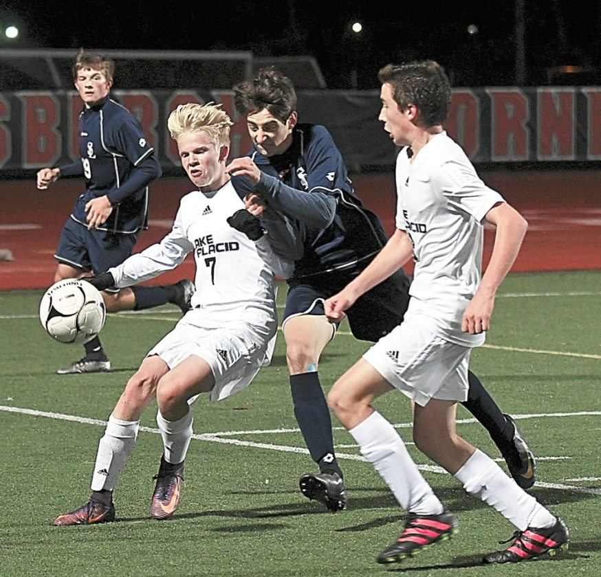 Lake Placid's Joose Kahkonen, left, and Matt Brandes battle for the ball with Colby Jenkinson of St. Lawrence Central during the second half of Wednesday's state regional semifinal match in Plattsburgh. The Blue Bombers won 1-0 to move into the state Class C quarterfinal round. (Enterprise photo — Lou Reuter)
