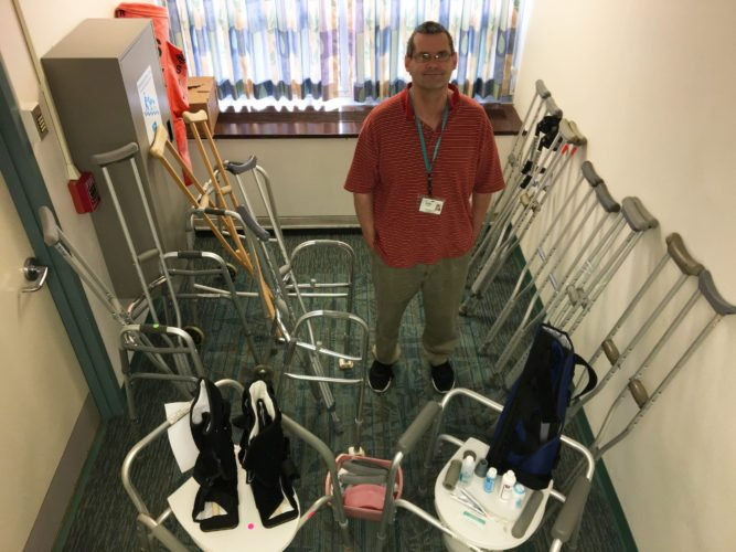 Jerry Stewart, rehab technician at Adirondack Medical Center in Saranac Lake, stands with donated home medical equipment and supplies bound for Nicaragua. (Photo provided — Adirondack Health)