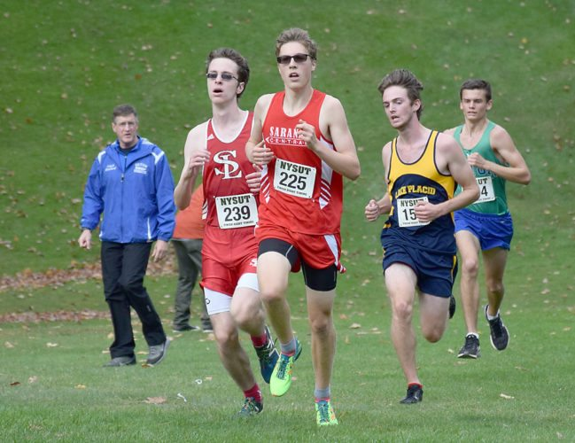Saranac Lake junior Anderson Gray, left, runs just behind Saranac's Andrew LePage as Scott Schulz of Lake Placid and Caleb Moore of Seton Catholic maintain the lead pack during Friday's Section VII championship race at Cobble Hill Golf Course in Elizabethtown. Gray went on to win the race with a sprint finish, while LePage was second, Moore was third and Schulz took fourth. (Enterprise photo — Justin A. Levine)