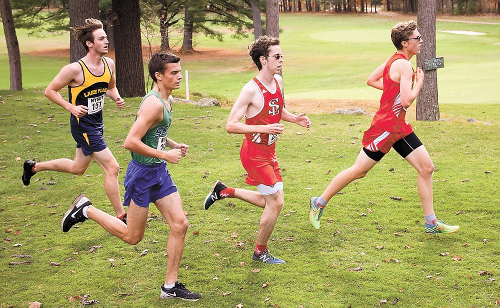 From left, Lake Placid's Scott Schulz, Seton Catholic's Caleb Moore, Saranac Lake's Anderson Gray and Saranac Central's Andrew LePage run in a pack during the Section VII cross country championships Friday in Elizabethtown. Gray won the race, followed by LePage, Moore and Schulz. (Enterprise photo — Justin A. Levine)