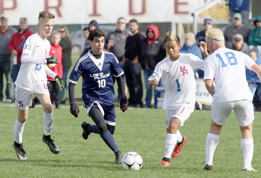 Joaquin Benavides controls the ball through a trio of Maple Hill players during Saturday's NYSPHSAA Class C quarterfinal game at Colonie High School. (Photo — Alicia Brandes)