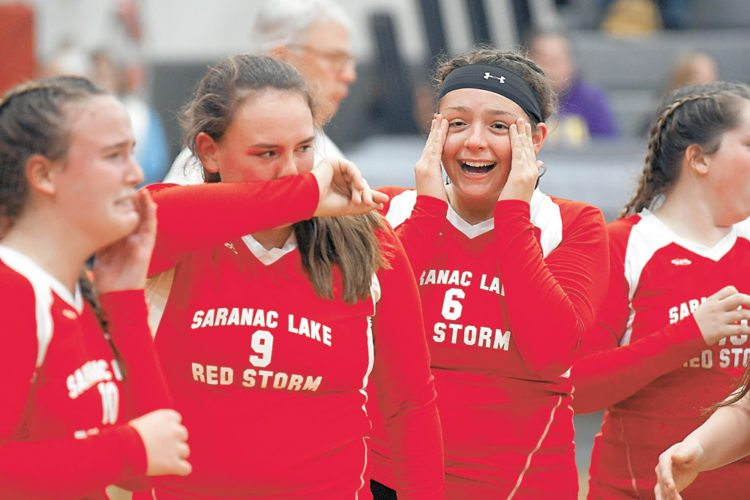 Saranac Lake players Madie Gay, Katie Gay and Nora Glover are overcome with emotion after their squad knocked off top-seeded Saranac Central Saturday in Beekmantown to win the first Section VII, Class C title in the history of Saranac Lake volleyball. (Enterprise photo — Lou Reuter)