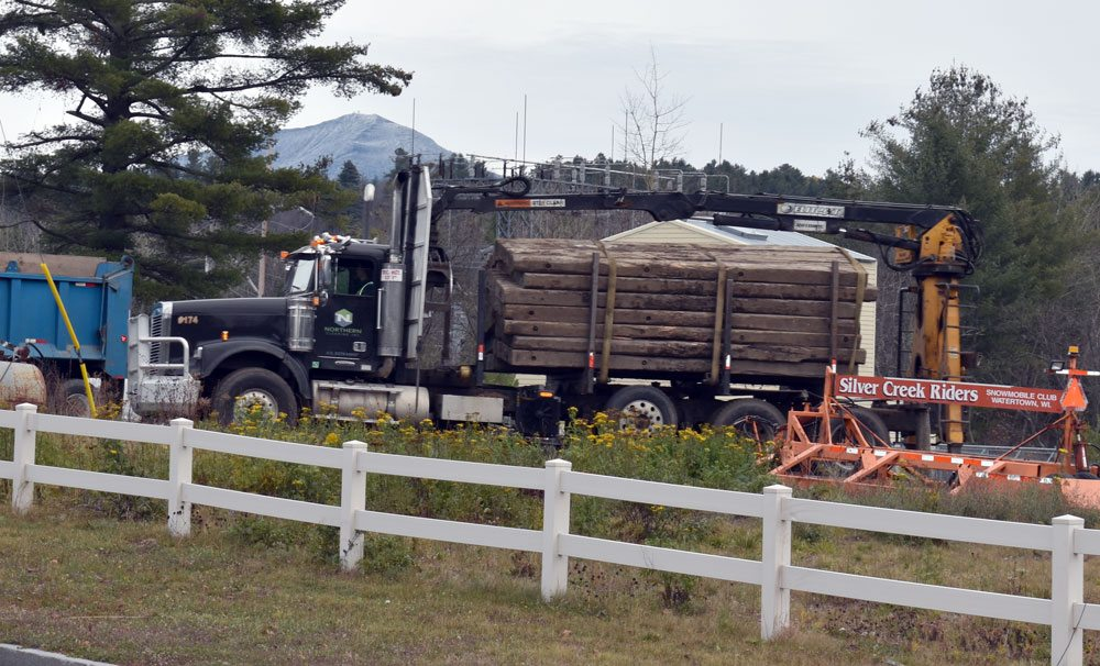 A truck brings more wooden beams to be stacked near Old Military Road in Lake Placid Tuesday. The beams will be used to aid in replacing six utility poles on the electrical line along the railroad tracks that feeds Lake Placid's electrical needs. (Enterprise photo — Griffin Kelly)