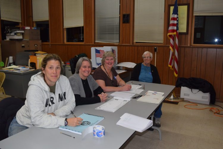 Jordanna Mallach of Saranac Lake, left, helps out as a poll inspector at the Franklin Town Hall in Vermontville Tuesday even though she was a council candidate in the town of Harrietstown. She was asked to help in Franklin due to a shortage of poll workers. She won her race in Harrietstown.  (Enterprise photo — Glynis Hart)