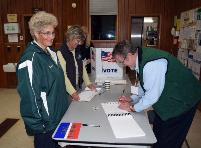 Rebecca Romeo, left, votes Tuesday at the Franklin Town Hall in Vermontville. (Enterprise photo — Glynis Hart)