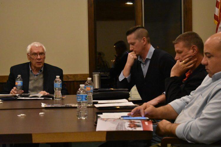 From left, Lake Placid village Mayor Craig Randall talks to Trustees Jason Leon and Scott Monroe, and Treasurer Paul Ellis Monday at a regular meeting of the village Board of Trustees. (Enterprise photo — Griffin Kelly)