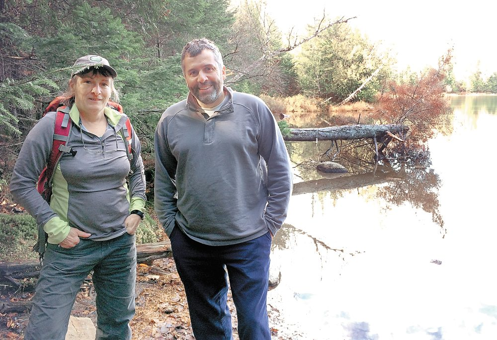 Sue Capone, left, and ALSC program manager Jed Dukett pose at Heart Lake in the High Peaks during a recent sampling trip to the small lake. (Enterprise photo — Justin A. Levine)
