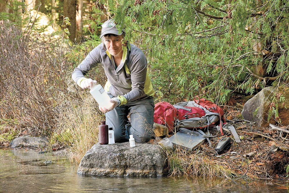 Sue Capone, a long-time Adirondack Lake Survey Corporation employee, takes a water sample at Heart Lake in the High Peaks in mid-October. (Enterprise photo — Justin A. Levine)