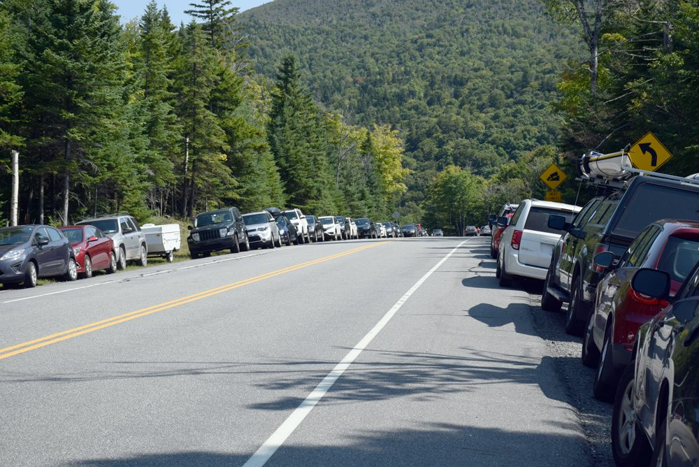 Hundreds of cars line the sides of state Route 73 outside of Lake Placid during Labor Day weekend last year. The DEC is proposing a 50-car parking area at Mount Van Hoevenberg to alleviate the congestion at Pitchoff and Cascade mountains. (Enterprise photo — Justin A. Levine)