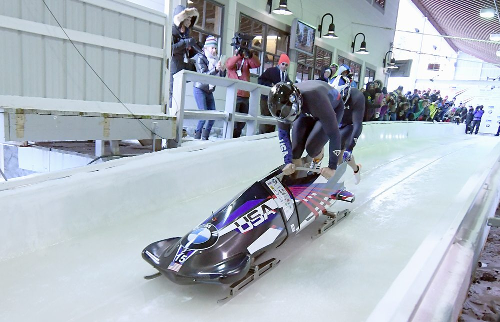 Justin Olsen hops into his sled while Evan Weinstock pushes as the U.S. pair begins its first of two runs in Friday's World Cup race. Olsen drove to a third-place finish, which was the first time he has reached the podium as a pilot. (Enterprise photo — Lou Reuter)