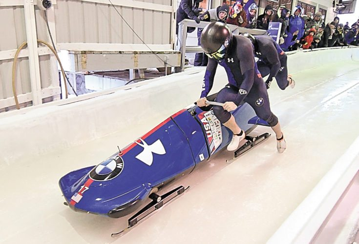 United States bobsled pilot Codie Bascue and brakeman Sam McGuffie push their sled to begin their first of two runs in Friday's World Cup competition at Mount Van Hoevenberg. The pair put down the fastest runs in both heats to claim the gold medal as the World Cup tour wrapped up its first week of competition. (Enterprise photo — Lou Reuter)