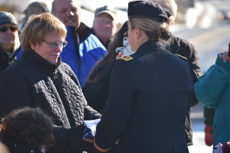 Jordana Mallach, right, presents a flag to veteran Lewis Conway's wife Saturday at the Veterans Day services in Lake Placid.  (Enterprise photo — Griffin Kelly)
