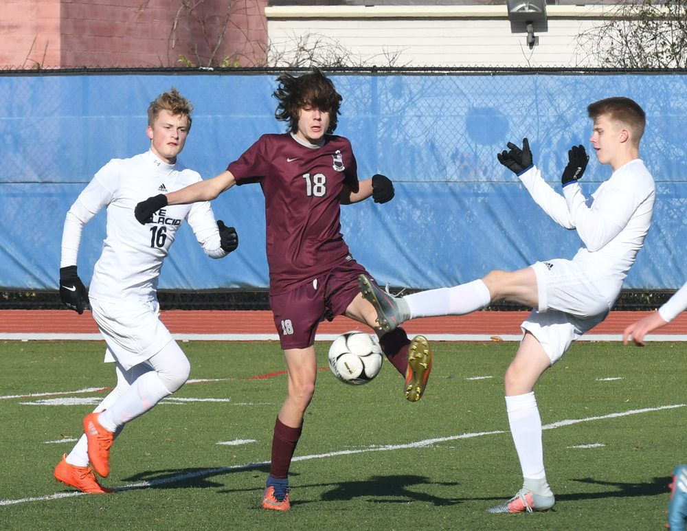 Lake Placid defenders Hayden Plank (16) and Jaso Hannula converge on Byron-Bergen forward Sam Pringle during the opening half of Saturday's state Class C semifinal match in Middletown. (Enterprise photo — Lou Reuter)