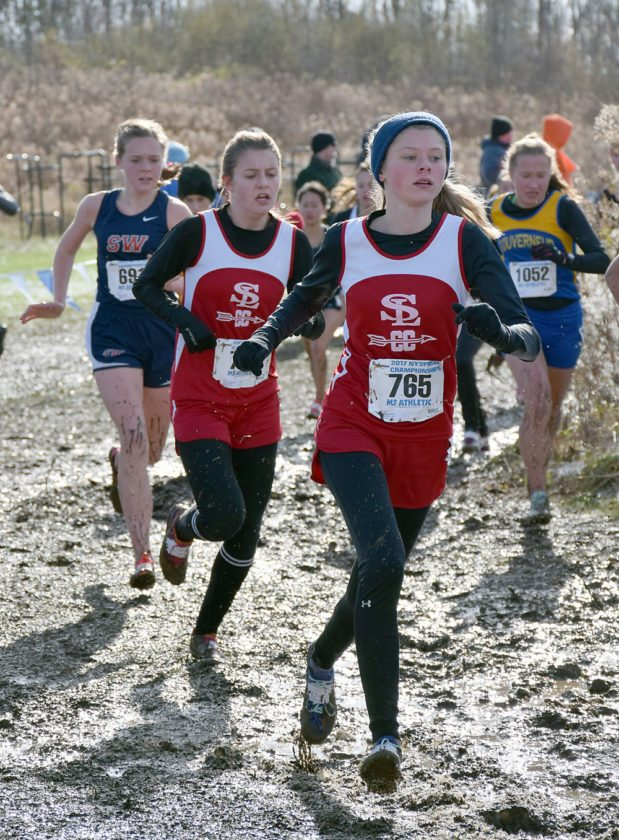 Saranac Lake freshman Gwen Mader, right, and senior Madison Grimone round a muddy corner during the girls Class C NYSPHSAA cross country championships Saturday in Ontario Center. Mader finished the race 66th with a time of 22:50.8 and Grimone placed 68th in 22:54.8. (Enterprise photo — Justin A. Levine)