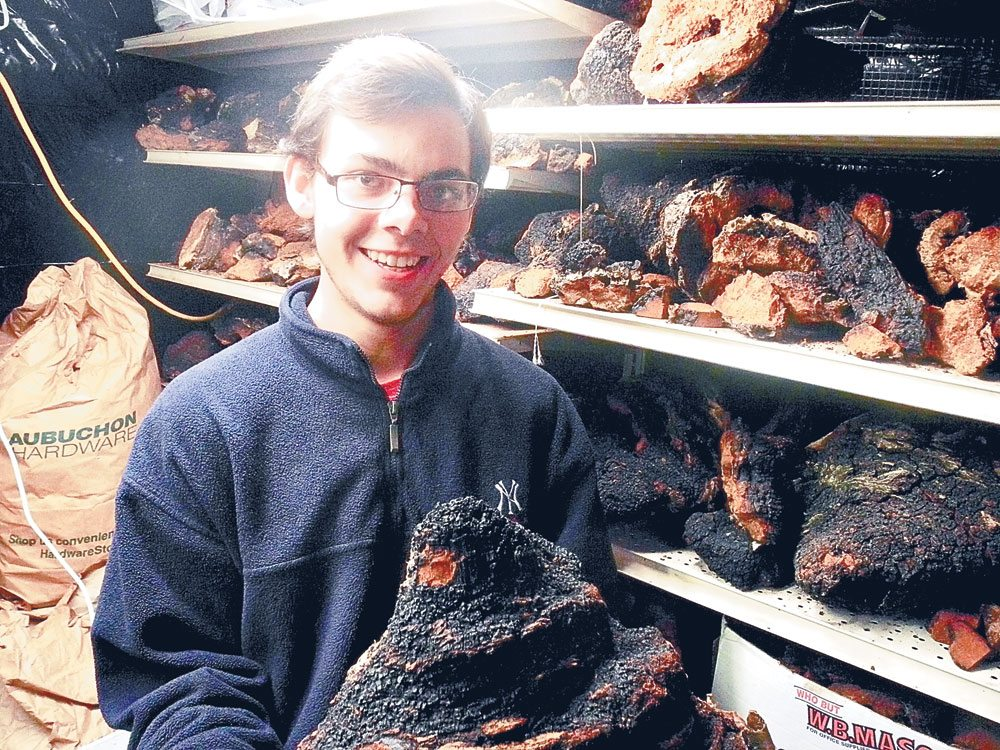 Garrett Kopp, the 19-year-old Tupper Laker behind the Birch Boys chaga tea company, holds a large 10-year-old lump of the unusual mushroom in his drying room where chaga is dehydrated before being ground into a powder. (Enterprise photo — Aaron Cerbone)