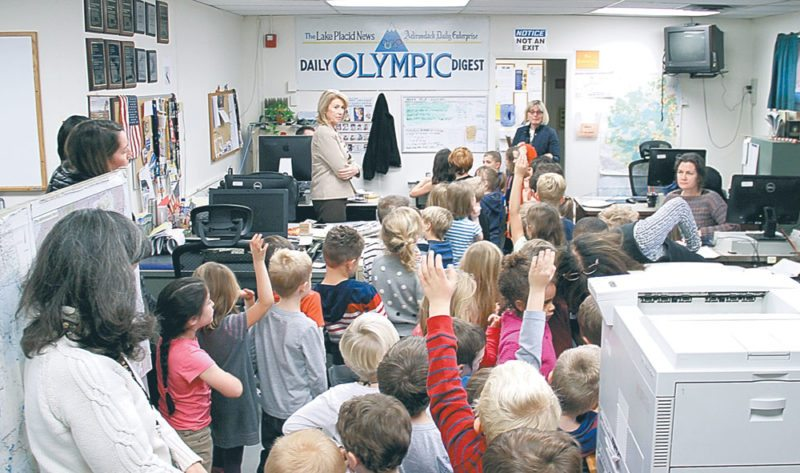 Adirondack Daily Enterprise and Lake Placid News Publisher Cathy Moore, standing under the Daily Olympic Digest sign, gives students in the Lake Placid Elementary School's kindergarten classes a tour of the Enterprise newsroom in Saranac Lake. Students learned all about how their hometown newspapers are made, from advertising to news and sports and the press room. This is one of the class's favorite field trips of the year, one teacher said. (Enterprise photo — Andy Flynn)