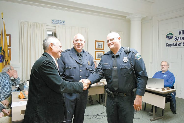 From left, Saranac Lake Mayor Clyde Rabideau and police Chief Charles Potthast congratulate police officer John Gay on his promotion to sergeant at Monday's village board meeting. Gay's father also served in the police department. (Enterprise photo —  Glynis Hart)