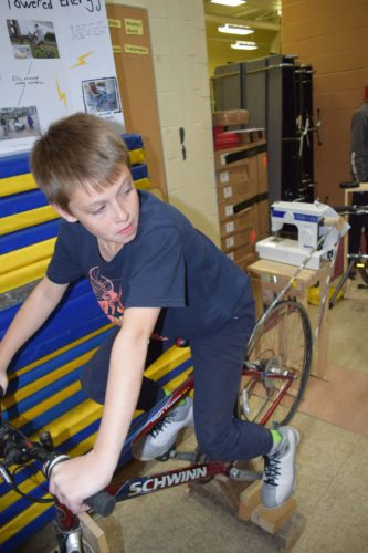 Sawyer Trudeau, an eighth-grader at Saranac Lake Middle School, pedals a bicycle he connected to a sewing machine, which runs using pedal power. His project was on display at the school's Harvest Dinner Wednesday.  (Enterprise photo — Glynis Hart)