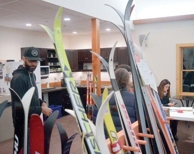 Jason Smith, who manages Dewey Mountain Recreation Center, talks with people bringing skis to be sold at the Dewey Mountain Ski Swap, from 9 to 11:30 a.m. today at the ski center on Route 3 in Saranac Lake. Dewey's annual sale focuses on nordic rather than alpine skis. (Enterprise photo — Aaron Cerbone)