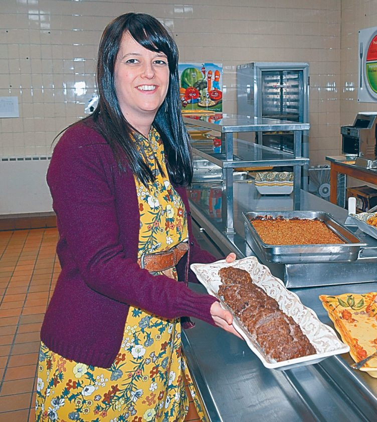 Teacher Christina Grant demonstrates some of the food at Saranac Lake Middle School's Harvest Dinner Wednesday evening, Nov. 15. (Enterprise photo — Glynis Hart)