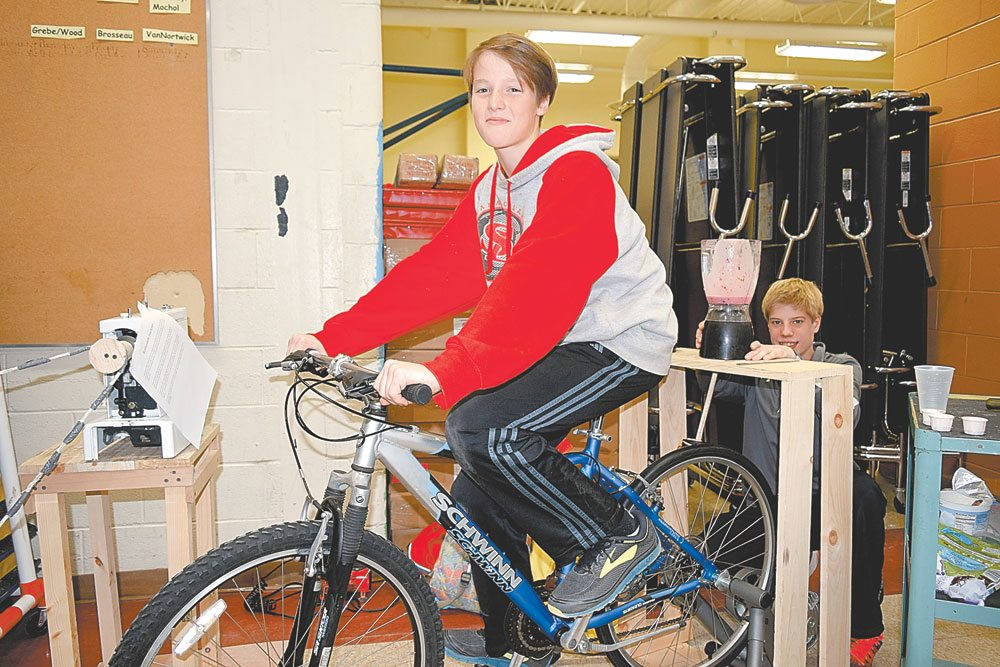 Students Levi Groves, on the bike, and Nate McCarthy demonstrate a machine they worked up in which pedaling a bicycle powers a blender that is used to make smoothies Wednesday evening, Nov. 15 at Saranac Lake Middle School. (Enterprise photo — Glynis Hart)