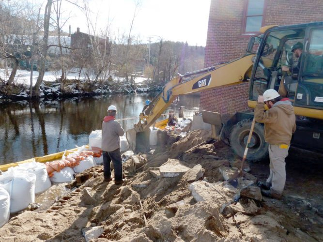 Construction workers demolish St. Regis Canoe Outfitters' retaining wall between the Saranac River and Dorsey Street Tuesday in Saranac Lake. Business owner Dave Cilley said the concrete wall, damaged in the spring 2011 flood, will be rebuild 6 feet back to allow a walkway along the river to give more room for staging boats and gear. The steps down to the river will also be rebuilt. (Enterprise photo — Peter Crowley)