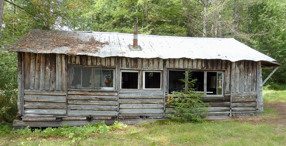 This old, abandoned log cabin hunting camp is situated on a high bank, overlooking a remote section of the Raquette River. With the end of the big game hunting season in sight, many camps will soon fall silent. (Photo provided — Joe Hackett)