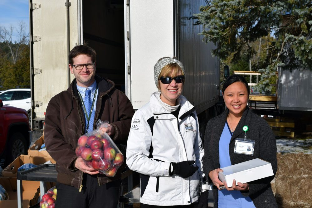 From left, Carl Bowen, director of nutritional services for Adirondack Health, Adirondack Health President and CEO Sylvia Getman and echocardiographer Rachel Davide show off some of the local produce at Adirondack Medical Center in Saranac Lake. (Enterprise photo — Glynis Hart)