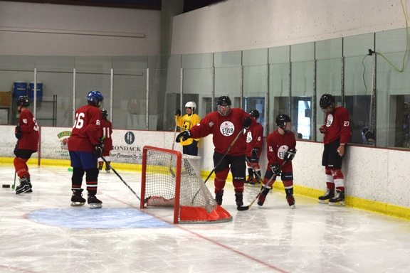 On the ice, everybody's equal. Veterans and kids worked on passing and shooting skills together.  (Enterprise photo — Glynis Hart)